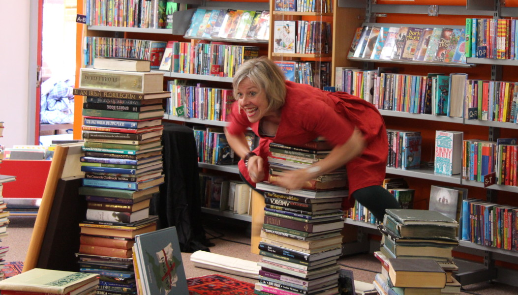 Image of An excited woman climbs on a stack of books in a library